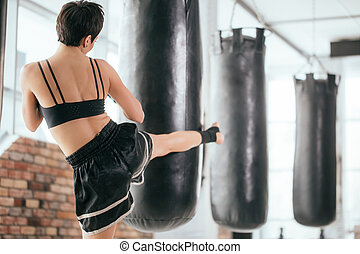 rear view photography of young woman athlete kicking boxing.