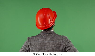 Rear view portrait of a contractor wearing hardhat looking...