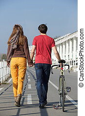 Rear view portrait of a young couple walking outdoors