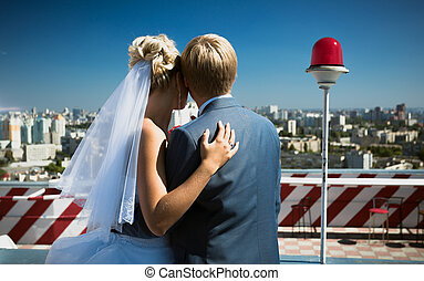 just married couple standing on roof top and looking at the city