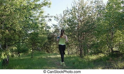 Rear view. Runner young woman running in park exercising outdoors fitness tracker wearable technology. Athlete girl jogging in park she running from the camera and listen to music in headphone on a smartfone