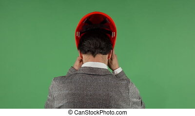 Rear view shot of a businessman putting on protective...