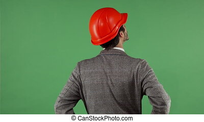 Rear view shot of a contactor wearing hardhat looking around on chromakey