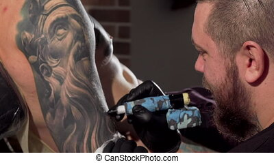 Rear view shot of a tattoist making tattoos on the arm of...