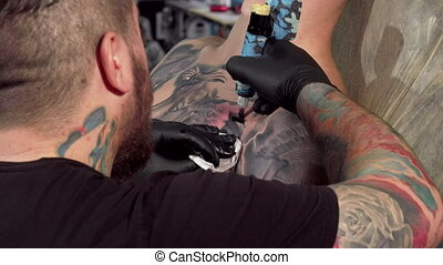 Rear view shot of a tattoo artist making a tattoo on chest...