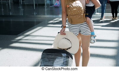 Rear view slow motion footage of beautiful woman holding little boy walking with suitcase in airport terminal