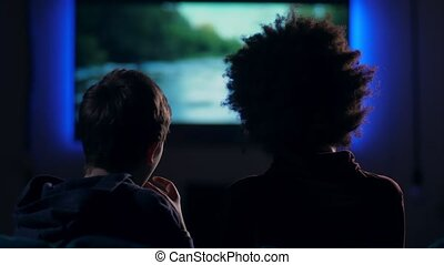 Rear view teen boys watching movie on screen - Back view...