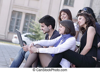 rear view. the group of friends of students with a laptop