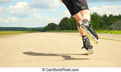 Rear view to inline skater in green running singlet ....
