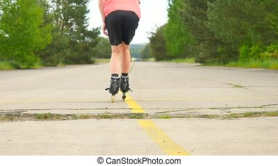 Rear view to inline skater in green running singlet . Outdoor inline skating on smooth asphalt in the forest. Light skin man is jumping on the road, moving with center of gravity.