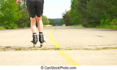 Rear view to inline skater in green running singlet . Outdoor inline skating on smooth asphalt in the forest. Light skin man skating on the road, moving with center of gravity.