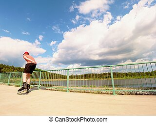 Rear view to inline skater in red t-shirt and black pants...