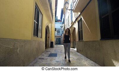 Rear view tourist woman Walking narrow streets of Barcelona...