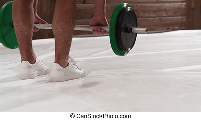 Rear view. With ray of light weightlifting young man bent gripping a black and green weight set, equipment for weight training concept. Weight loss, healthy lifestyle concept. 4K footage,