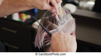 Alternative cool hair salon. Rear view close up of a Caucasian male hairdresser working in a hair salon, holding brush, colouring hair of a Caucasian female client in slow motion