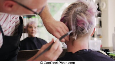 Alternative cool hair salon. Rear view close up of a Caucasian male hairdresser working in a hair salon, holding brush, colouring hair of a Caucasian female client, reflecting in a mirror, in slow motion