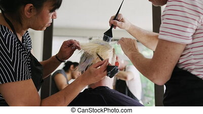 Alternative cool hair salon. Rear view of a Caucasian male and mixed race female hairdressers working in a hair salon, holding brushes, colouring hair of a Caucasian female client in slow motion