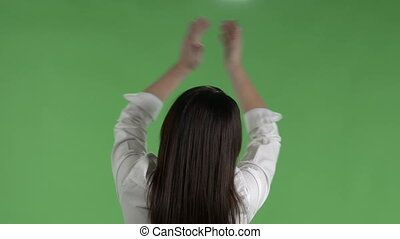 Rear view woman in white shirt clapping hands above her head green screen