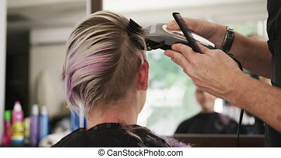 Rear view woman shaving her hair at the hairdresser - ...