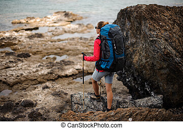 Rear view woman standing on the rocks with hiking backpack