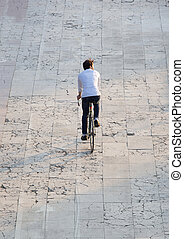 Rear view young man cycling on street