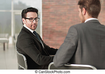 rear view.two businessman sitting at his Desk