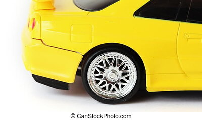 rear wheel of yellow toy radio-controlled car slips on white background