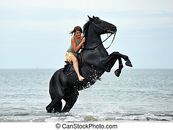 young woman and her beautiful black stallion rearing up in the sea