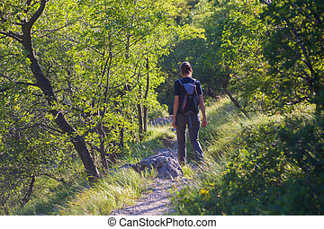 Rearview of a woman hiker with backpacks walking in the Mountain path