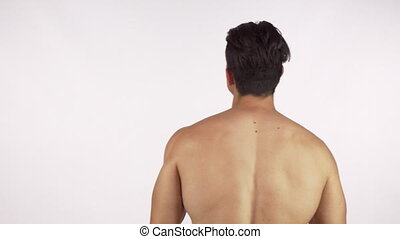 Rearview shot of a muscular shirtless man flexing his back...