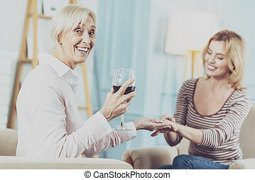 Cheerful aged woman drinking a glass of wine