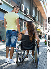 couple at wheelchair walk through city