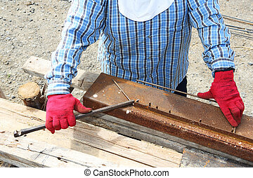 Rebar bending by worker on rusty jig in construction site
