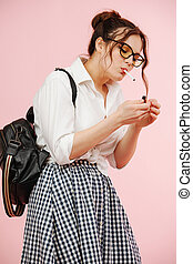 Rebellious young woman in a schoolgirl outfit smoking cigarette, lighting it. Over pink background. She wears glasses, two buns on her head, checkered skirt and white dress shirt.