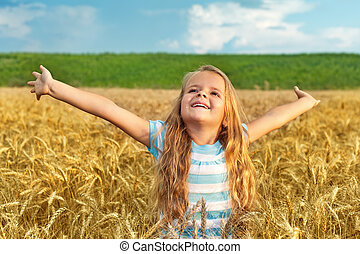 Receive blessings of nature - Little girl standing in wheat...