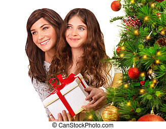 Receive Christmas gift, isolated on white background, decorated festive evergreen tree, mother with daughter at home on New Year eve