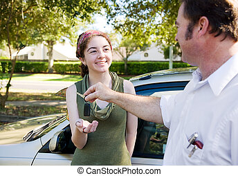 Receiving Car Keys - Young woman being handed the car keys...