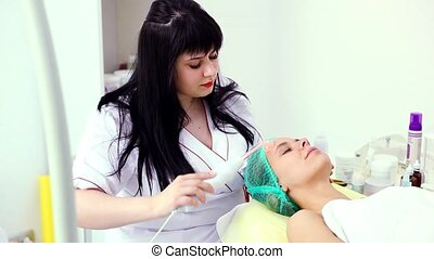 Receiving electric darsonval facial massage procedure.