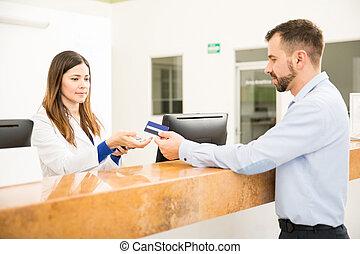recepcionista, levando, pagamento, com, cartão crédito