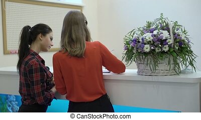 Reception in clinic hospital, receptionist and patient...