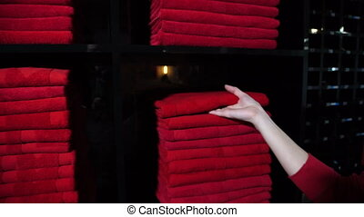 Reception staff takes towel from stack for client from warehouse.