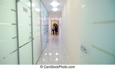 Receptionist and doctor with client in hospital entering...