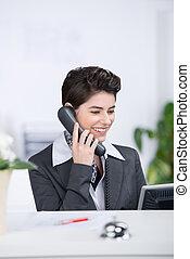 Receptionist Conversing On Landline Phone At Counter - Happy...