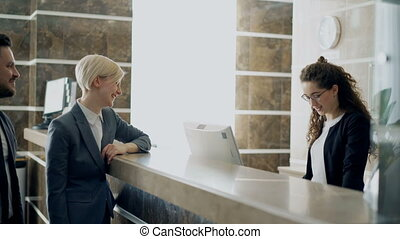 Receptionist girl talking with arrived businessman and...
