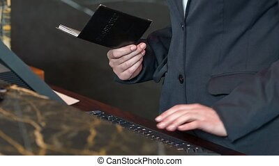 Receptionist holding passport while registrating guest -...