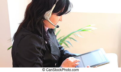 Receptionist On The Phone - Adult woman with headset talking...