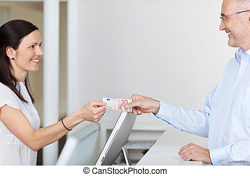Receptionist Receiving 10 Euro From Patient