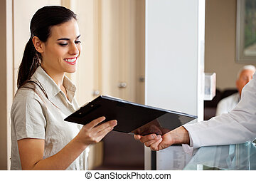 Receptionist Taking Clipboard From Doctor - Happy young ...