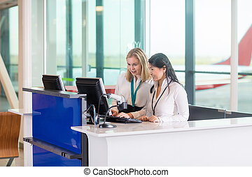 Receptionists Using Computer At Counter In Airport