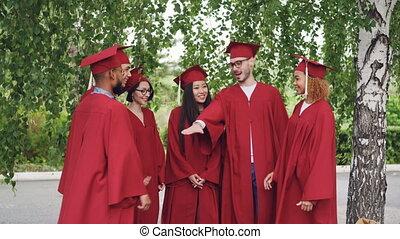 recevoir diplôme, alors, mains, groupe, étudiants, mortar-boards., applaudir, remise de diplomes, ensemble, debout, multiracial, célébrer, mettre, dehors, robes, porter, amis, joyeux
